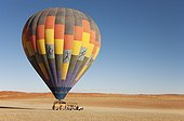 NamibRand Nature Reserve ; Namibia - After having landed, the ground crew pulled the basket with the passengers to the nearby truck, while the pilot skilfully keeps the hot-air balloon on the right height. Namib Desert, NamibRand Nature Reserve, Namibia.