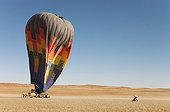 NamibRand Nature Reserve ; Namibia - After having landed, the ground crew assists the passengers at getting out of the basket of the hot-air balloon while another 2 assistants try to drag the balloon to the ground. Namib Desert, NamibRand Nature Reserve, Namibia.
