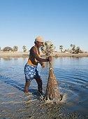 Vegetable Ivory Palm - Namibia ; Namibia - Owambo girl fishing in a shallow pool (oshana) which characterise the region. In the background Makalani palm trees (Hyphaene petersiana). Omusati region, northern Namibia.