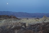 Full moon - California Death Valley National Park ; Full moon at dawn over the Panamint Range and the Death Valley. Seen from Zabriskie Point with the badlands of Gower Gulch in the foreground and the Manly Beacon crag on the right. Death Valley National Park, California, USA.