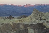 Sunrise - California Death Valley National Park ; The rocky outcrop of Manly Beacon (on the right) rises above the badlands below Zabriskie Point. In the background the Death Valley and the Panamint Range at sunrise. Death Valley National Park, California, USA.