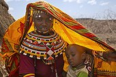 Rendille girl in traditional dress with child Kenya ; They are nomads who tend camels, sheep, goats and cattle.