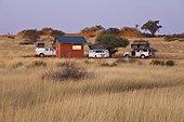 Safari vehicules in the desert of Kalahari in Namibia