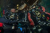 Aquanauts  enter the wet porch - Aquarius Reef Base Florida ; Aquanauts re-filling their tanks in the wet porch; though a direct bypass hose attached to their regulators, divers can connect their empty tank onto an air filling station, while still carrying their tanks on the back.