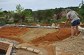 Laying the substrate of an ecological swimming pool - France ; The installation of the substrate allows the planting of the plants around the pool.