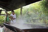 Manufacture of Cassava flour - Amapa Brazil Amazon  ; Use a scraper called rodo to aerate flour Cassava during drying and cooking <br>People Ribeirinhos