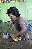 Child eating cassava flour and Acai juice - Brazil ; Child 4 year<br>People ribeirinhos <br>Araguari river