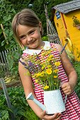 Little girl and garden shed in a flowered kitchen garden