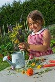 Little girl in a flowered kitchen garden