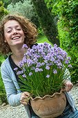 Young girl and chive in pot in a garden