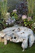 Teak root coffee table in a garden ; Landscaper: Pierre-Alexandre RISSER