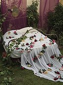 Romantic style bed with bedsheets and rose petals in exhibit