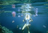 Female swimer surronded by Jellyfish Palagia noctiluca