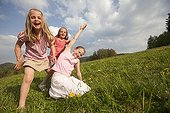 Young girls playing in a meadow in spring - Alsace France