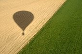 Shadow of a hot air-balloon on a field - France