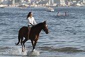 Young girl riding bareback in the sea - Senegal