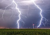 Lightning and wind in the eveningin  countryside - France ; A wind turbine is struck by lightning and another an upward leader on a light.<br>The impact of lightning that hits the ground is 180 meters away from the photographer.<br>Two pictures superimposed 30 seconds