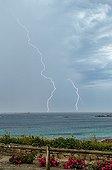 Orage au dessus de la Manche en été - Pointe Bretonne France ; De nombreux impacts de foudre frappent la mer et les côtes. Certains sont à quelques centaines de mètres du photographe. Superposition de deux photos.