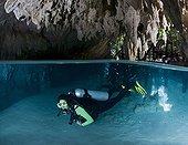 Diver in the Cenote Pet Cemetery - Yucatan Mexico ; scuba diver begins a cenote dive, having entered the water through a hole in the jungle floor. This underground chamber leads to passageways and rooms spectacularly decorated with limestone formations.