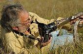 Homme photographiant un Cobra indien dans l'herbe ; Photographe : Daniel Heuclin