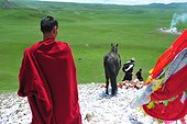 Rider praying before the race when Lapsté - Tibet China  ; Equestrian Festival Lapste <br>Before racing, the riders and their horses are praying gods by turning around a stupa and throwing sacred papers in the air.