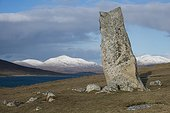 Stone MacLeod - Harris Hebrides ; Menhir above Traigh Iar beach on the Isle of Harris in Scotland. We see the snowy mountains of Harris and one end of the island of Taransay left.