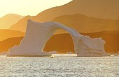 Denmark. Greenland. West coast. Sunset on an arch shaped iceberg in the straight of Vaigat, near the village of Saqqaq.