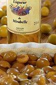 liquor bottle and pie Mirabelle plum (Prunus domestica syriaca), Lorraine, France