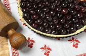 Cherries pie furnace outlet in its mold sheet , tablecloth with cherry motifs and wooden rolling pin, France