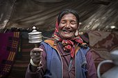 Woman with prayer wheel inside a Yack wool tent, Surroundings of Korzok, Leh, Ladakh, Himalayas, India