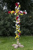 Easter cross covered in colourful flowers outside Cotswold church UK