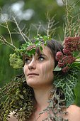 Young woman with crown flowers on her head - living in harmony with nature - reconnecting with nature