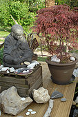 Tibetan monk statue in meditation at the edge of a Zen garden pond, Jardin de l'Écriture et de la Poésie, Garden of Writing and Poetry, Eure et Loir, France