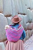 Quechua woman carrying a baby lama on her back, Cuzco, Peru