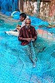Fishing in Kerala. Repairing the nets in the Beypore port