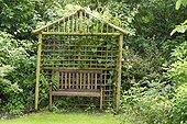 Wooden bench under an arbor. Garden of the Notre-Dame d'Autrey abbey, Vosges. La France.