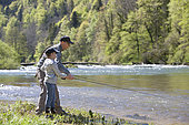 Fly fisherman and child learning, River Doubs, Goumois, Franche-Comté, France