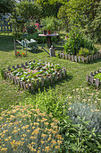 Vegetable garden square, wheelbarrow, small table and aromatic plants in June, Provence, France