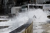 Elderly person surprised by a big wave during a big tide in Saint-Valery-en-Caux, Normandy, France