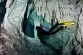 scuba diver (model released) swimming through caverns and tunnels accessed from the surface via a cenote in the jungle. This underground river system spiders across the Yucatan Peninsula, an eerie realm known by the local Maya people as Xilbalba which translates into Place of Fear