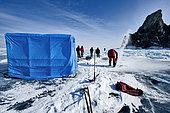 Cutting a hole in the ice before a dive - Lake Baikal, Siberia, Russia