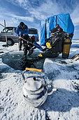 Scuba divers preparing for ice diving, Lake Baikal, Siberia, Russia