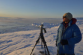Explorer setting his camera for a timelaps of the Sun, Greenland, Februaury 2016, Scoresbysund Fjord
