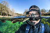 Selfie with a Common toad (Bufo bufo) swimming at the surface, Buèges spring, Occitania, France
