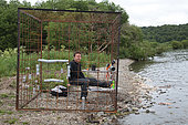 Photographer in a submerged protection cage for Kamtchatka bear (Ursus arctos beringianus) - Lake Kourile, Kamchatka, Russia