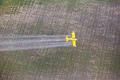 Aerial photography of small plane spraying on crop field, Bahìa de Cadiz, Spain