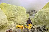 Indonesia, Java Island, East Java province, Kawah Ijen volcano, Miner preparing sulfur blocs