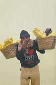 Indonesia, Java Island, East Java province, Kawah Ijen volcano, Miner carrying baskets of sulfur