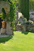 An alley surrounded with cypresses in front of a lawn bed, Saint Adrien garden, Hérault, France