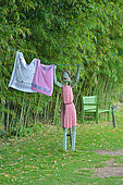 Wooden statue of someone hanging out the washing in the St Adrian Garden, Hérault, France